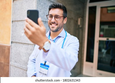 Young handsome hispanic doctor wearing uniform and stethoscope smiling happy Standing with smile on face using smartphone at town street.