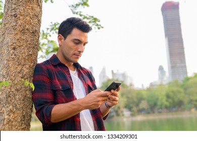 Young handsome Hispanic hipster man using phone beside tree at the park