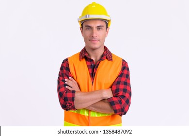 Young handsome Hispanic man construction worker with arms crossed