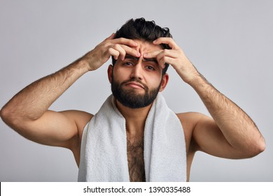 Young handsome Hispanic man has problem with skin.beraded sexy man pressing out, squeeze out pimples in the bathroom. close up photo. isolated gray background