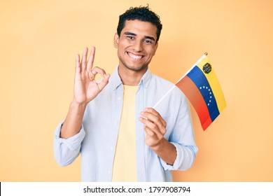 Young handsome hispanic man holding venezuelan flag doing ok sign with fingers, smiling friendly gesturing excellent symbol