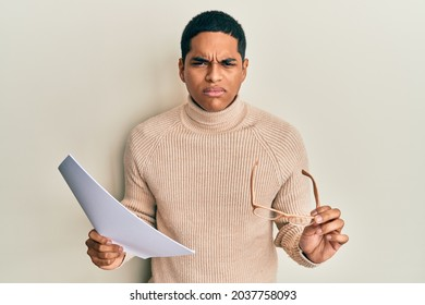Young handsome hispanic man holding blank paper and glasses skeptic and nervous, frowning upset because of problem. negative person.