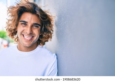 Young handsome hispanic man smiling happy leaning on the wall at street of city