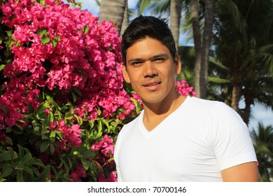 Young handsome hispanic man standing in front of Bougainvillea flowers and palm trees