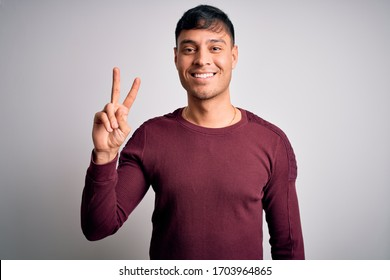 Young handsome hispanic man wearing casual shirt standing over white isolated background showing and pointing up with fingers number two while smiling confident and happy.