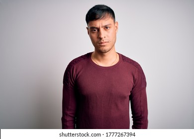 Young handsome hispanic man wearing casual shirt standing over white isolated background skeptic and nervous, frowning upset because of problem. Negative person.