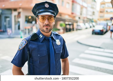 Young handsome hispanic policeman wearing police uniform smiling happy Standing with smile on face at town street.