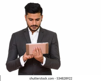 Young handsome Indian businessman using digital tablet
