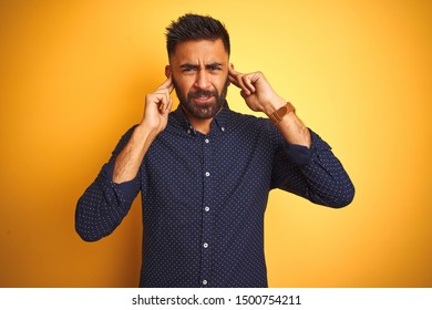 Young handsome indian businessman wearing shirt over isolated yellow background covering ears with fingers with annoyed expression for the noise of loud music. Deaf concept.