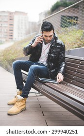 Young handsome indian contemporary businessman seated on a bench in a park using tablet talking smartphone with one earphone already on looking downward - business, work, technology concept
