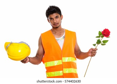 Young handsome Indian man construction worker holding safety helmet and red rose ready for Valentine's day