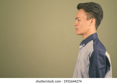 Young handsome Indian man looking smart against colored background