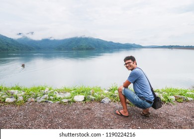 Young handsome indian man relax with nature cloudy sky mountain and lake view during travel at Thailand
