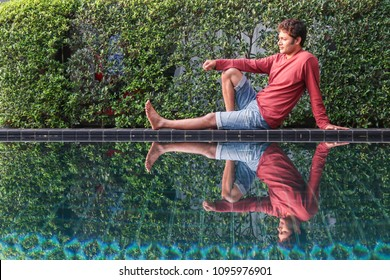 Young handsome indian man relaxing at swimming pool on vacation
