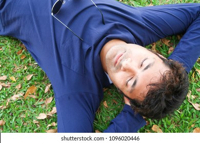 Young handsome indian man sleeping on green grass on holiday
