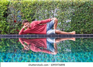 Young handsome indian man smiling and relaxing at swimming pool on vacation