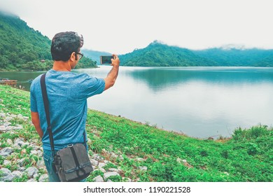 Young handsome indian man take photo of nature cloudy sky mountain and lake view by mobile on his vacation travel at Thailand