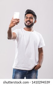 Young handsome Indian man taking selfie with mobile phone