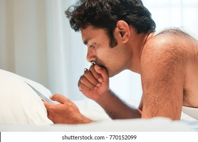 Young handsome Indian man thinking  when looking at mobile phone on bed