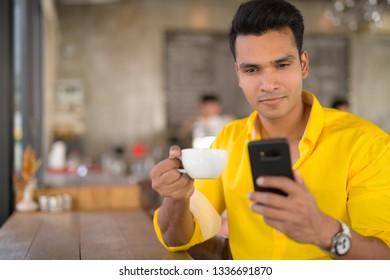 Young handsome Indian man using phone and sitting by the window at cafe