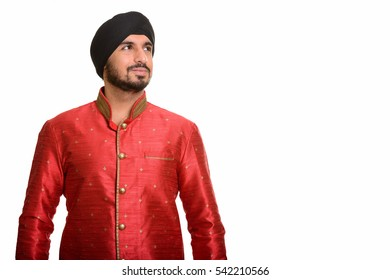 Young handsome Indian Sikh man thinking while wearing traditional clothes isolated against white background
