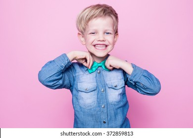Young handsome kid smiling with blue shirt and butterfly tie. Studio portrait over pink background
