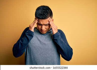 Young handsome latin man wearing casual t-shirt standing over yellow background with hand on head for pain in head because stress. Suffering migraine.