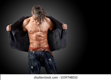Young handsome with long blond hair, macho man, unbuttoned jacket, naked muscular chest and torso. Fashion concept, beautiful sports model, dark background. Copy space