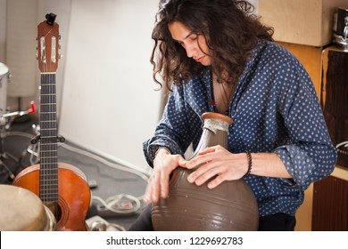 Young handsome long haired gypsy styled percussionist smiling portrait enjoying while playing udu on a music studio with speakers, drums, flamenco drum box and spanish guitar on the background.