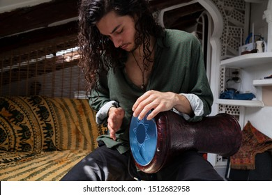 Young handsome long haired man feeling his passion for music playing an arabic darbuka on a penthouse alternative studio background.