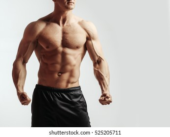 young handsome macho man bodybuilder with sexy muscular athletic body with bare torso and strong belly with six packs or abs in studio on white background, copy space