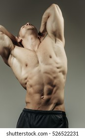 young handsome macho man bodybuilder with sexy muscular athletic body with bare torso and strong belly with six packs or abs in studio on grey background