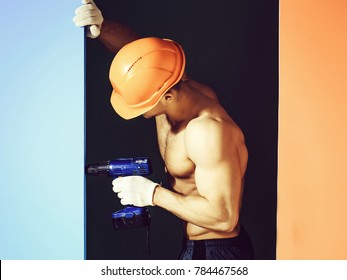 young handsome macho man builder with sexy muscular athletic strong body has bare torso and strong belly with six packs or abs in orange hard hat or helmet holds punch on colorful background