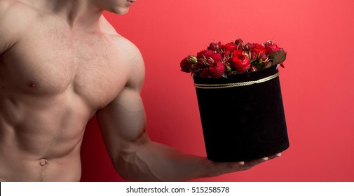 young handsome macho man gardener with sexy muscular athletic body with bare torso and strong belly with six packs or abs holds red rose flowers bouquet in box on studio background