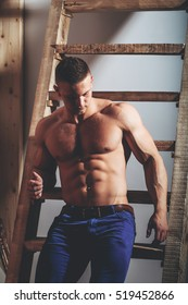 young handsome macho man in jeans with sexy muscular athletic body with bare torso and strong belly with six packs or abs in studio at wooden ladder