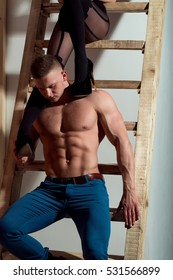 young handsome macho man in jeans with sexy muscular athletic body with bare torso and strong belly with six packs or abs and female legs in black shoes and stockings in studio at wooden ladder