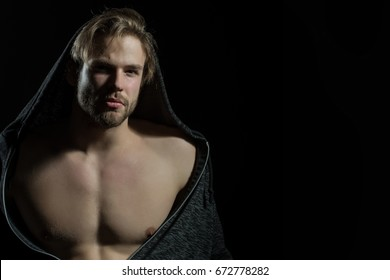 Young handsome macho man with open jacket revealing muscular chest. Blonde guy with beard in fashionable sweatshirt, men's clothing. Fit young man with beautiful torso on black background, copy space