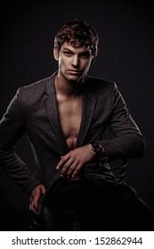 Young handsome macho man sitting in studio.