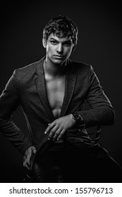 Young handsome macho man sitting in studio. Black and white  shoot
