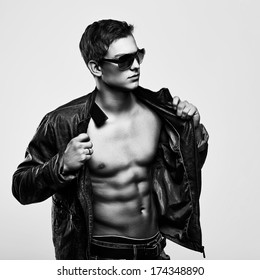 Young handsome macho man in sunglasses with open leather jacket revealing muscular chest and torso