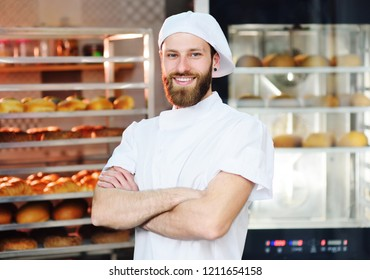 Young handsome male baker in white uniform against a background of baking and bread.