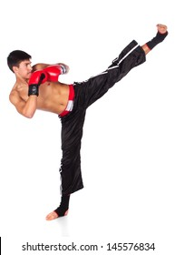 Young handsome male caucasian kickboxer wearing red boxing gloves and kickboxing gear isolated on a white background