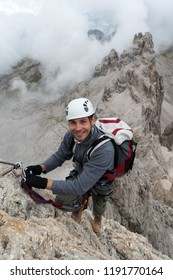 young handsome male climber on a steep and exposed rock face climbs a Via Ferrata in Alta Badia in the South Tyrol