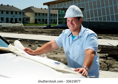 Young Handsome Male Construction Site Foreman, Checking The Blueprints
