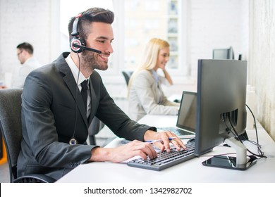 Young handsome male customer support operator in businesswear with headset talking with client while working on computer at his workplace