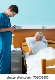 Young handsome male doctor in uniform with phonendoscope on his neck looking at a thermometer of his patient, who is lying in the hospital bed in the hospital ward. Healthcare concept