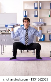 Young handsome male employee doing exercises in the office