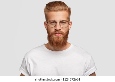 Young handsome male hipster has thick ginger beard and mustache, trendy haircut, looks seriously directly at you, wears spectacles and white t shirt, isolated over studio wall. Masculinity concept