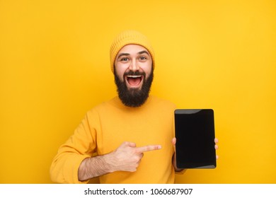 Young handsome male model in yellow outfit demonstrating modern tablet looking excited.