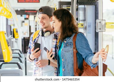 Young handsome male student helping attractive helpless female buying the ticket with ticket machine in modern tram during ride. Communication, acquaintance, friendship concept.